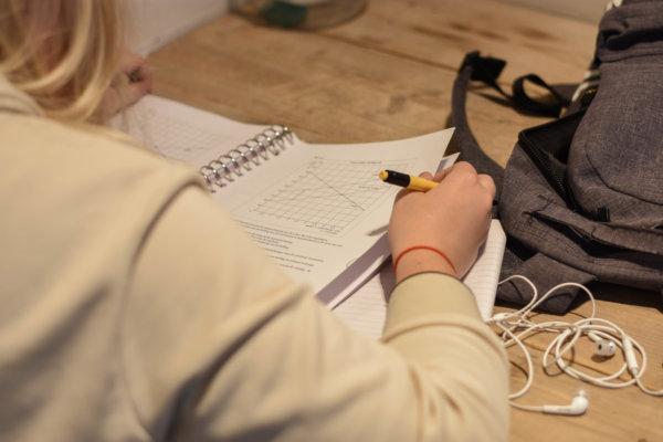 op deze foto is een meisje te zien dat haar huiswerk aan het maken is. Ze is zich aan het voorbereiden voor de examens.
