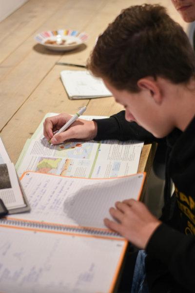 Op de foto een jongen te zien die bezig is met zijn huiswerk.